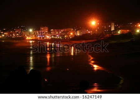 beach-town at night wit the reflection of the light on the water - stock photo