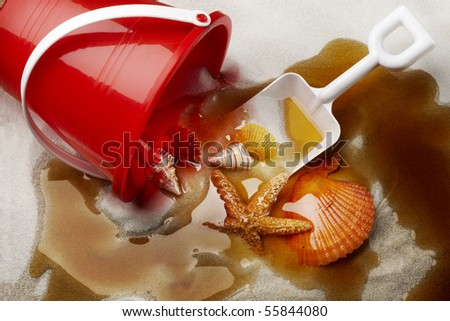 Beach toys and sea shells on sand covered with oil - stock photo