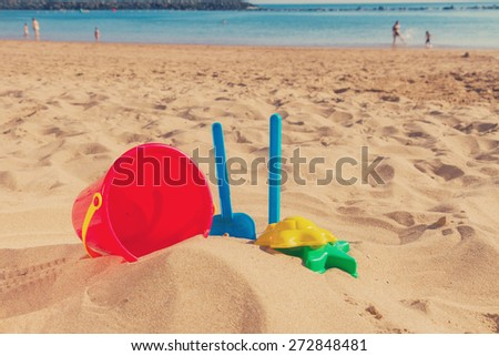 beach toys in sand on sea shore at sunny summer day, retro toned  - stock photo