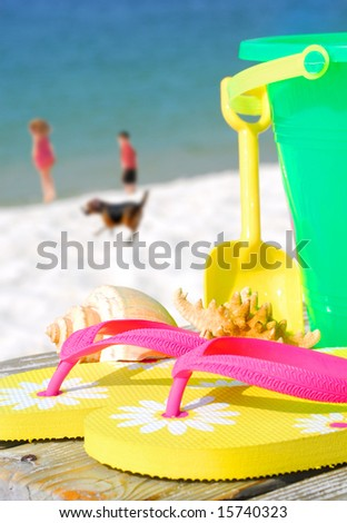 Beach toys on boardwalk with children and dog at shore in distance - stock photo