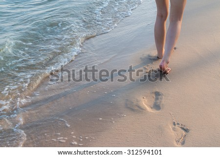Beach travel alone - woman walking alone on sand beach leaving footprints in the sand Closeup detail of female feet and golden sand background - stock photo