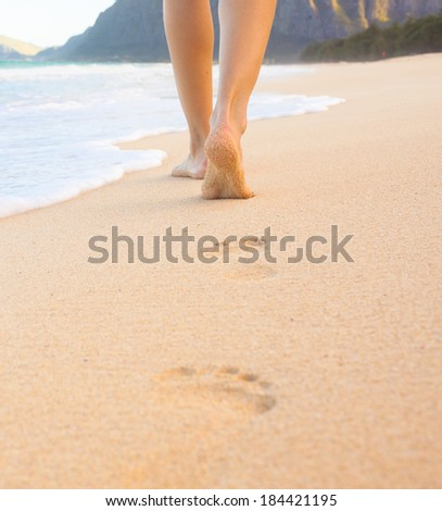 Beach travel - beautiful girl walking on sand beach leaving footprints in the sand. Closeup detail of female feet and golden sand on beach in Hawaii. - stock photo