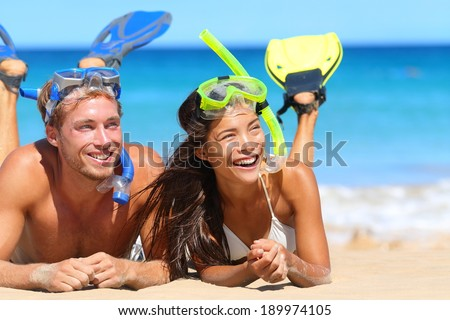 Beach travel couple having fun snorkeling. Happy young multiracial couple lying on summer beach sand with snorkel equipment looking to side at copy space after swimming with fins and mask on vacation. - stock photo