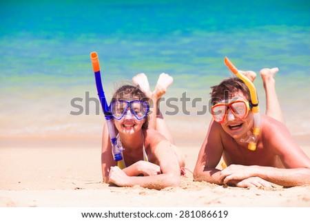 Beach travel couple having fun snorkeling, lying on summer beach sand with snorkel equipment  - stock photo