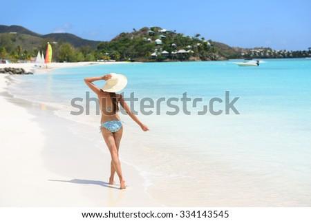 Beach travel vacation woman in bikini wearing beach hat, joyful and free on holidays on Jolly Beach, Antigua Girl on travel vacation holidays having fun. Asian Chinese Caucasian female model. - stock photo