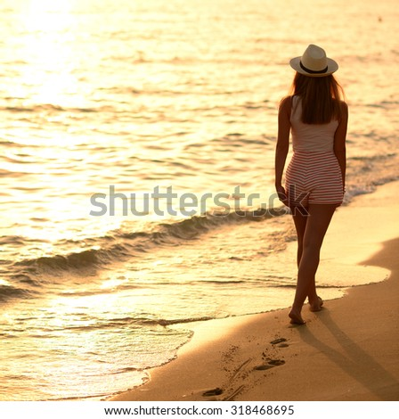 Beach travel - woman walking on sand beach leaving footprints in the sand - stock photo