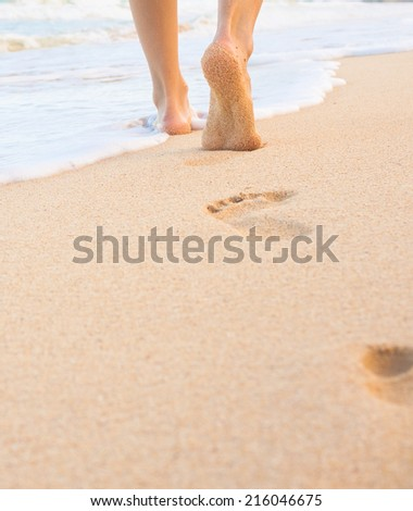 Beach travel - woman walking on sandy beach leaving footprints in the sand. Closeup detail of female feet and golden sand on beach in Hawaii. - stock photo