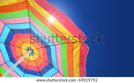 Beach umbrella against sunny blue sky on a summer day. Copy space. - stock photo