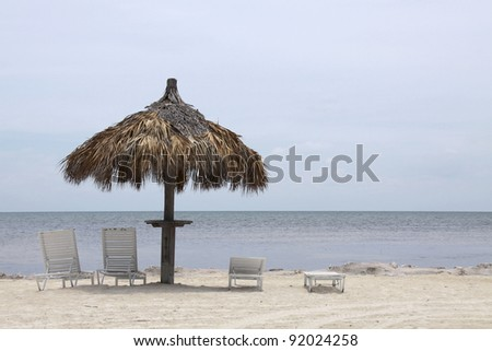 Beach umbrella and chairs on the Florida Keys sea - stock photo
