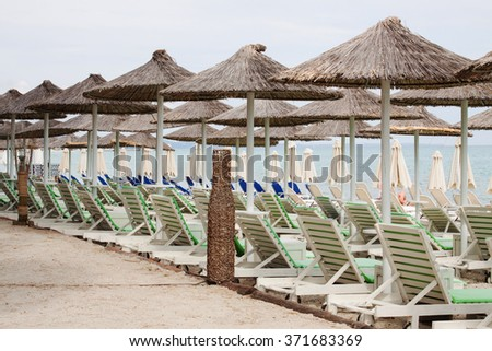 Beach umbrella and plastic deck chairs on the beach,Greek , pefkohori..