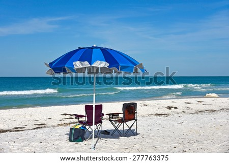Beach Umbrella and Two Chairs on the Beach - stock photo