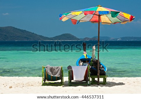 Beach umbrella chairs and boat in Komodo beach in Coral island, Thailand