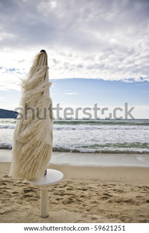beach umbrella during a windy day - stock photo