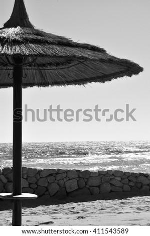 Beach umbrella made of straw on the beach. Black and white toning. - stock photo