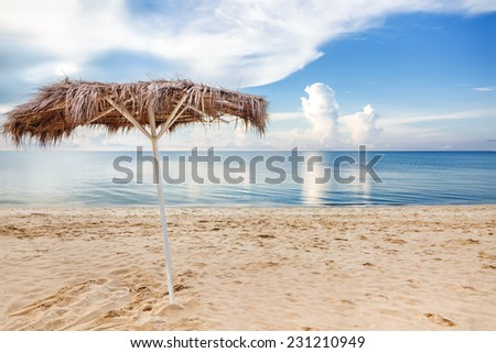 Beach umbrella on a empty deserted beach - stock photo