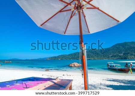Beach umbrella on a sunny day, sea in background - stock photo