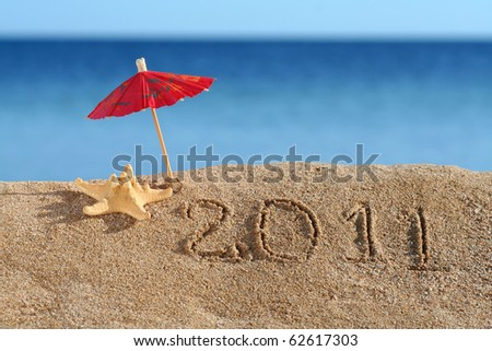 Beach Umbrella standing in the Sand with a Starfish near. New year 2011 at the beach!