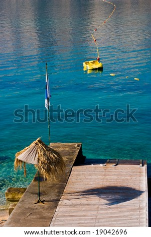 Beach umbrella with pedalo - stock photo