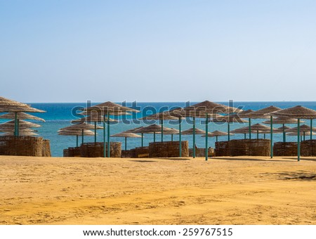 Beach umbrellas and beach chair on a tropical sand beach. Resort vacation on a tropic beach of summertime. - stock photo