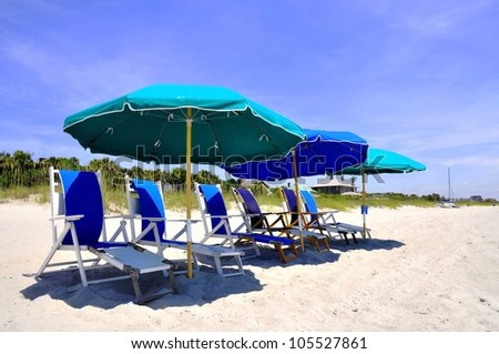 Beach Umbrellas and Beach Chairs waiting for sunbathers - stock photo
