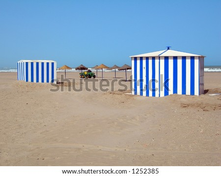 Beach umbrellas and car between two cabins - stock photo