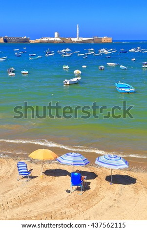 Beach umbrellas and chair by the Atlantic ocean and distant castle of San Sebastian, Cadiz, Andalusia, Spain - stock photo