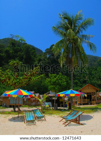 Beach umbrellas and chairs at a tropical beach of Phi-Phi island, Thailand - stock photo