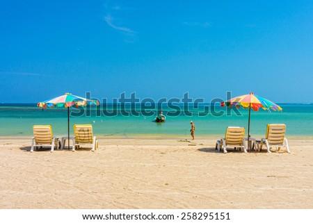 Beach umbrellas and sunbathe seats on Phuket sand beach in Southern Thailand - stock photo