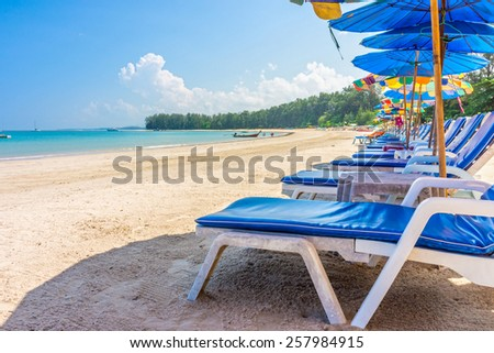 Beach umbrellas and sunbathing seats on Phuket sand beach in Southern Thailand - stock photo