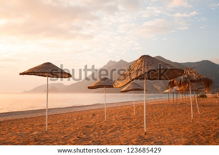 Beach umbrellas at sunset in the Mediterranean Sea Sea and mountains in the background. - stock photo