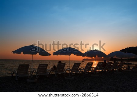 Beach umbrellas in a line on a sunset - stock photo