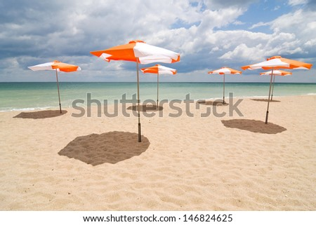 Beach umbrellas on sand beach. Concept for rest, relaxation, holidays, spa, resort.  - stock photo