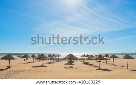 Beach umbrellas on the the beautiful empty beach. - stock photo