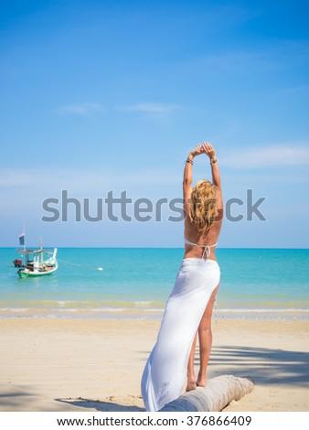 Beach vacation. Beautiful woman  enjoying perfect sunny day walking on the beach. Happiness and bliss. - stock photo