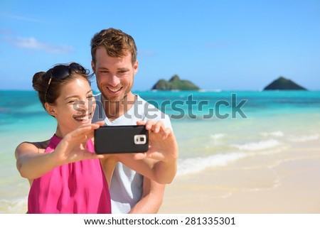 Beach vacation couple taking selfie photograph using smartphone, Lanikai beach, Oahu, Hawaii, USA with Mokulua Islands. Couple holding smart phone camera. Young beautiful multicultural Asian Caucasian - stock photo