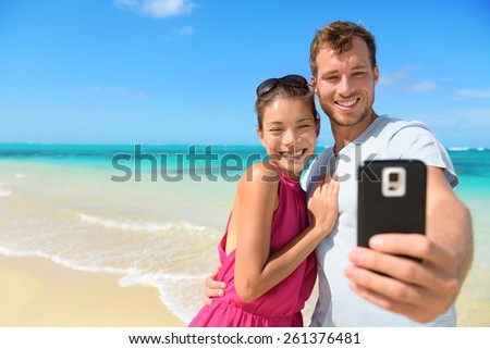 Beach vacation couple taking selfie photograph using smartphone relaxing and having fun holding smart phone camera. Young beautiful multicultural Asian Caucasian couple on summer beach. - stock photo