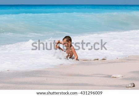 Beach vacation dream. Handsome young boy enjoying in beautiful tropical beach, running and playing with waves.