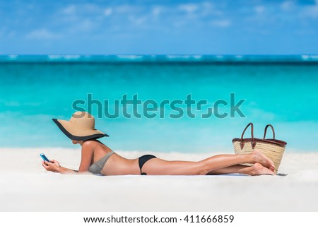 Beach vacation girl using mobile phone app texting sms or sharing photos on social media during summer travel holiday. Bikini woman relaxing sunbathing on sand lying on towel wearing sun hat.  - stock photo