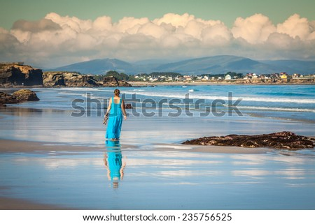 Beach vacation. Girl walking along a beach in the Spain - stock photo