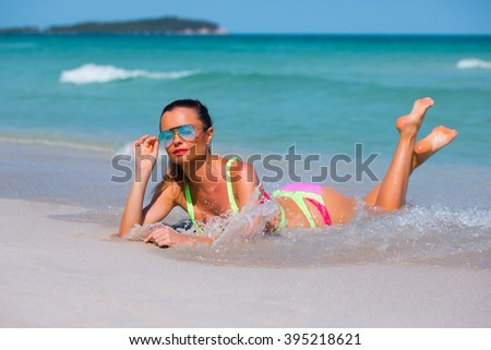 Beach vacation. Hot beautiful woman in sunglasses and bikini is lying on the sand near the sea