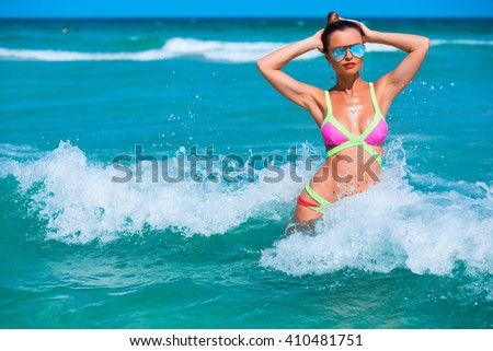 Beach vacation. Hot beautiful woman in sunglasses and bikini sending in the sea and smile