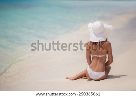 Beach vacation. Hot beautiful woman in sunhat and bikini standing with her arms raised to her head enjoying looking view of beach ocean on hot summer day. Photo from Hapuna beach, Big Island, Hawaii. - stock photo