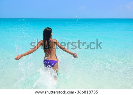 Beach vacation in tropical travel destination. Sexy woman in bikini feeling free swimming splashing water in blue ocean enjoying her sunny holidays. Concept of people having fun under the sun. - stock photo