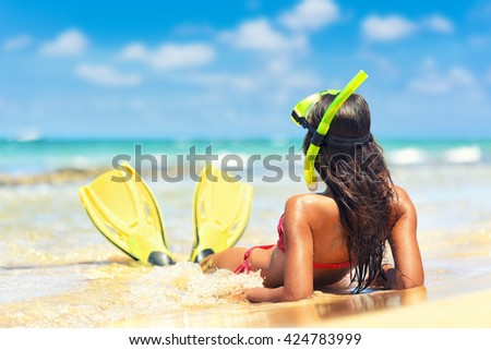 Beach vacation snorkel girl snorkeling with mask and fins. Bikini woman relaxing on summer holidays lying down in water after snorkelling with snorkel tuba and flippers sun tanning.