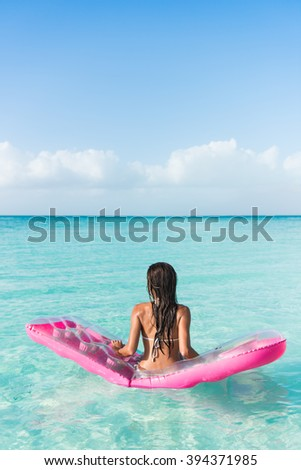 Beach vacation woman relaxing on ocean water bed. Beautiful woman from the back sitting on a pink pool float air mattress looking at view of the perfect turquoise pristine sea in tropical destination. - stock photo