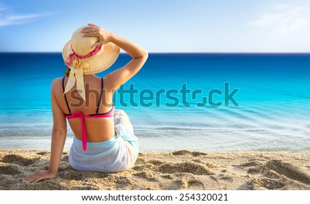 Beach vacation, young woman in sunhat and bikini sitting with her arm raised to her head enjoying looking view of beach ocean on hot summer day. - stock photo