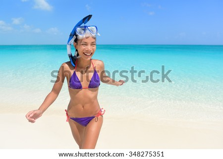 Beach vacations - Asian woman swimming having fun. Beautiful sexy young female adult running out of the water in snorkel scuba mask and purple bikini laughing during her travel holidays. - stock photo