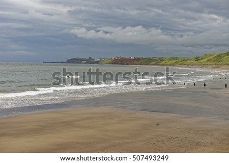 Beach view under a threatening sky from Sandsend to Whitby in North Yorkshire, England