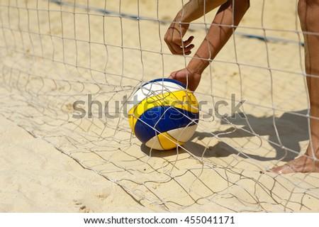 Beach volley ball: man picks up a ball - stock photo