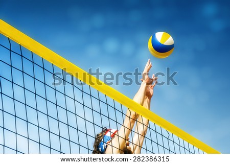 Beach volley ball player jumps on the net and tries to  blocks the ball - stock photo